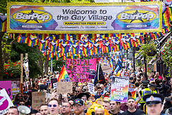 """© Licensed to London News Pictures . 28/08/2021. Manchester, UK. A banner reading """" Radical love is free unlike pride """" is carried along the protest route as it passes along Canal Street in Manchester's Gay Village . People take part in a Reclaim Pride march through Manchester City Centre , in opposition to the management of the city's """"official"""" Manchester Pride charity festival . The Manchester Pride charity parade was cancelled in 2020 due to Coronavirus . An """"equality march"""" organised by Manchester Pride charity was due to take place on Deansgate as the protest passed through the Gay Village . Protesters object to Manchester Pride charity's withdrawal of funding for the LGBT Foundation's condom distribution scheme and HIV charity George House Trust as well as increasing commercialisation of the annual event . Photo credit: Joel Goodman/LNP"""