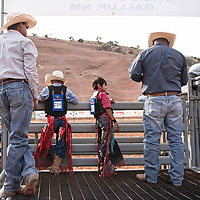 Riders lean against a chute as they wait for their turn to compete, Wednesday, June 12 at Red Rock Park during the Gallup Lions Club youth rodeo.