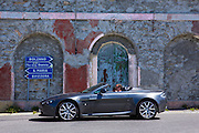 Driver in Aston Martin V8 Volante passes signpost on The Stelvio Pass, Passo dello Stelvio, Stilfser Joch, in Italy