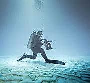 Underwater photographer on the sandy ocean bottom in Cozumel, Mexico