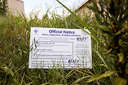 29 August 2015. Lower 9th Ward, New Orleans, Louisiana.<br /> Hurricane Katrina 10th anniversary memorials.  <br /> An official notice languishes in the grass and weeds of an overgrown, abandoned lot. A reminder of the storm a decade earlier.<br /> Photo credit©; Charlie Varley/varleypix.com.