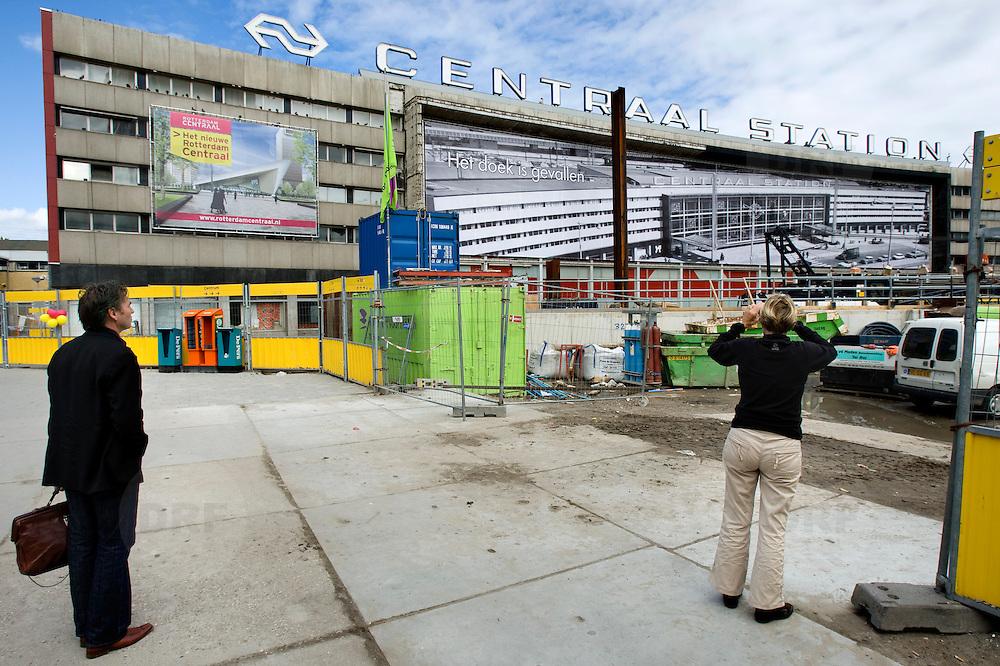 """Nederland Rotterdam 3 september 2007 20070903 .Voorbijgangers/ reizigers fotograferen en bekijken de vertrouwde oude hal van het voormalige centraal station nog een keer voordat het definitief gesloopt zal worden.  ."""" Het doek is gevallen """" Zondag 2 september is het doek letterlijk doek gevallen voor het in 1957 geopende gebouw. Over enkele weken wordt de schepping van architect Sybold van Ravesteyn gesloopt en komt op het Stationsplein een nieuwe OV-terminal, die na 2011 ruim 300.000 reizigers per dag moet kunnen verwerken. Voorbijgangers maken een foto van het oude bekende centraal station, dat sinds 1957 dienst heeft gedaan. Een gloednieuw station zal op deze plek verrijzen. ..Het tijdelijke station dat de periode overbrugt tussen de sloop van het oude Rotterdam CS en de bouw van een nieuw station, kost 12 miljoen euro. Dat is een schijntje vergeleken met het half miljard waarop het nieuwe is begroot. De bedoeling is dat de tijdelijke bebouwing in februari klaar is. Het blijft open tot 2010. Het oude gebouw maakt plaats voor vijf tijdelijke. Daarvan zijn er vier voor de reizigers en een voor het personeel van de Spoorwegpolitie. ..Tijdelijk Rotterdam Centraal.1 september 2007..Alle treinreizigers opgelet! Vanaf 2 september sta je voor een dichte deur als je bij Rotterdam Centraal op de trein wilt stappen. Tenzij je de ingang van het tijdelijke Rotterdam Centraal al gevonden hebt. ..Naast het oude vertrouwde station staat al een tijdje een groot blauw gebouw en vanaf 2 september kun je daar op je trein stappen. Je kunt er zelfs een kopje koffie halen, of kleine boodschappen doen. Alle winkels zijn namelijk gewoon verplaatst naar het grootste tijdelijke station van Nederland...Het Centraal Station was al een hele tijd een grote bouwput, want er wordt heel hard gewerkt aan een nieuw, beter en vooral moderner station. Maar omdat afscheid nemen altijd zo moeilijk is, vindt er op 12 september een soort ode aan het station en de architect Sybold van Ravesteyn plaats. De"""