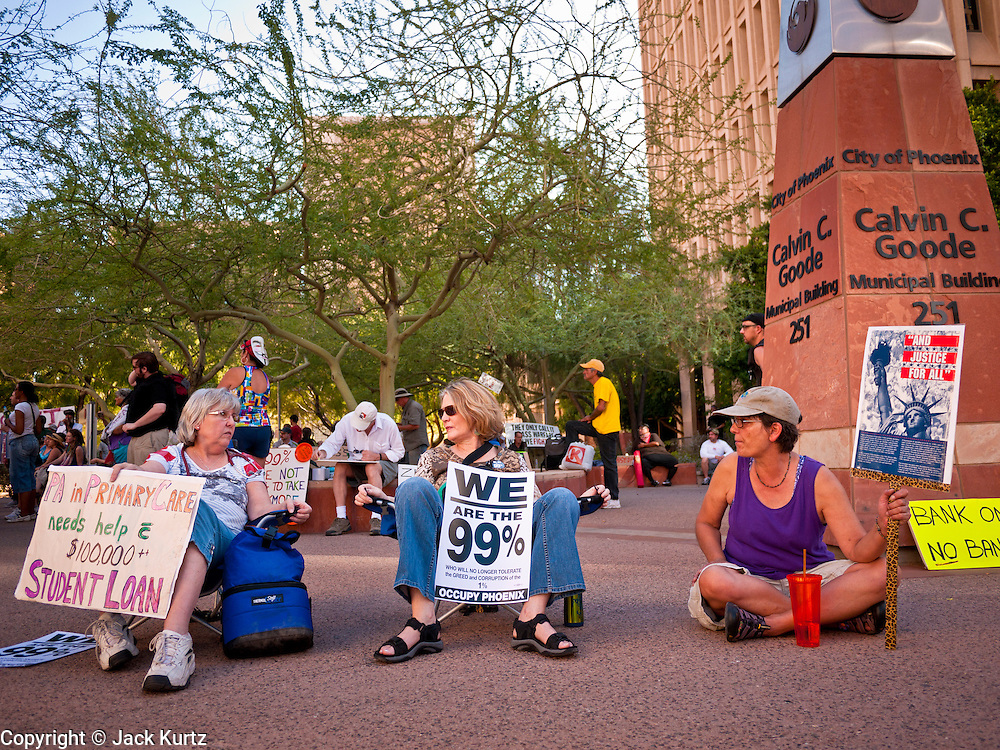 16 OCTOBER 2011 - PHOENIX, AZ: Women sit on the sidewalk at the Occupy Phoenix protest in downtown Phoenix, AZ, Sunday. About 200 people continued the Occupy Phoenix protest in downtown Phoenix Sunday afternoon. The protest peaked Saturday afternoon at about 2,000 people. Nearly 50 people were arrested late Saturday night on misdemeanor trespassing charges when they tried to camp in a park near downtown and on Sunday the crowd dwindled to 200. Protesters hope to continue the protest through Monday by marching around downtown and picketing banks in the area.    PHOTO BY JACK KURTZ