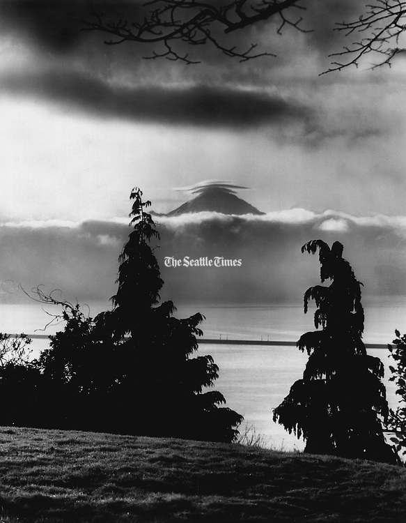 Mount Rainier appeared in the clear, cold air with a halo of clouds. The view was from the Madrona Park area. The Mercer Island Floating Bridge<br /> appears in the mid-ground. (Josef Scaylea / The Seattle Times, 1964)