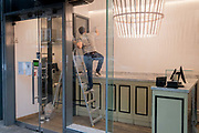 A man balances on some stepladders while decorating and refurbishing the interior of a retail business in Covent Garden, during the third lockdown of the Coronavirus pandemic, on 22 February 2021, in London, England.
