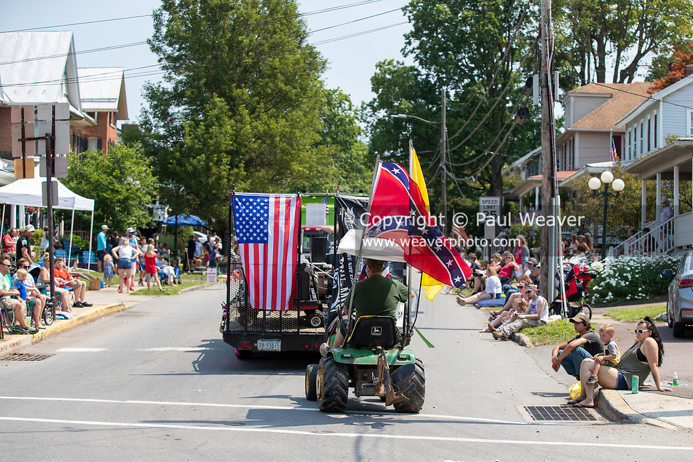 A man drives a lawn tractor with a confederate flag in the Independence Day parade in Millville, Pennsylvania on July 5, 2021.