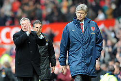 Manchester United manager Alex Ferguson (left) applauds as Arsenal manager Arsene Wenger walks off dejected following the Barclays Premier League match at Old Trafford, Manchester.