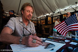David Uhl working on a watercolor of Michael Lichter at Destination Daytona during Daytona Bike Week. Ormond Beach, FL. USA. Monday March 12, 2018. Photography ©2018 Michael Lichter.