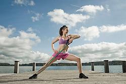 Woman woman exercising with resistance band, Woerthsee, Bavaria, Germany
