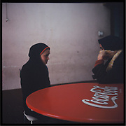 Young women wearing hijab sit in the table in the women's section at a restaurant in Kabul.