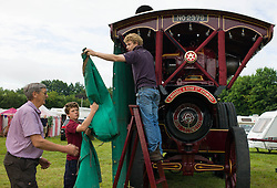 © Licensed to London News Pictures. 01/08/2013<br /> <br /> Pickering, Yorkshire, United Kingdom<br /> <br /> Owners of a steam engine remove the protective covers on the morning of the 61st annual Pickering traction engine rally in North Yorkshire. The event has the largest line up of Showman's engines and fairground organs in the north of England and boasts over a thousand vintage and classic cars, commercials, tractors and motorcycles, arena attractions, a fun fair, steam rollers, steam ploughing and along with food and craft marquees the event is the largest event of it's type in the north of England.<br /> <br /> Photo credit : Ian Forsyth/LNP© Licensed to London News Pictures. 01/08/2013