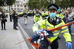 A Metropolitan Police officer tries to prevent press photographers taking photographs of a climate activist from Extinction Rebellion who had occupied a road around Parliament Square during a Back The Bill rally on 1st September 2020 in London, United Kingdom. Extinction Rebellion activists are attending a series of September Rebellion protests around the UK to call on politicians to back the Climate and Ecological Emergency Bill (CEE Bill) which requires, among other measures, a serious plan to deal with the UK's share of emissions and to halt critical rises in global temperatures and for ordinary people to be involved in future environmental planning by means of a Citizens' Assembly.