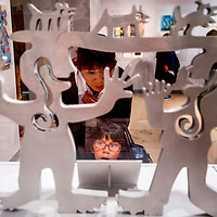 """071813       Cable Hoover<br /> <br /> Kyli Jesus, bottom, and her aunt Joanne Barton look at a sculpture by artist Melanie Yazzie during the opening of Yazzie's exhibit """"Connecting Cultures: The Four Directions"""" at the Navajo Nation Museum in Window Rock Thursday."""