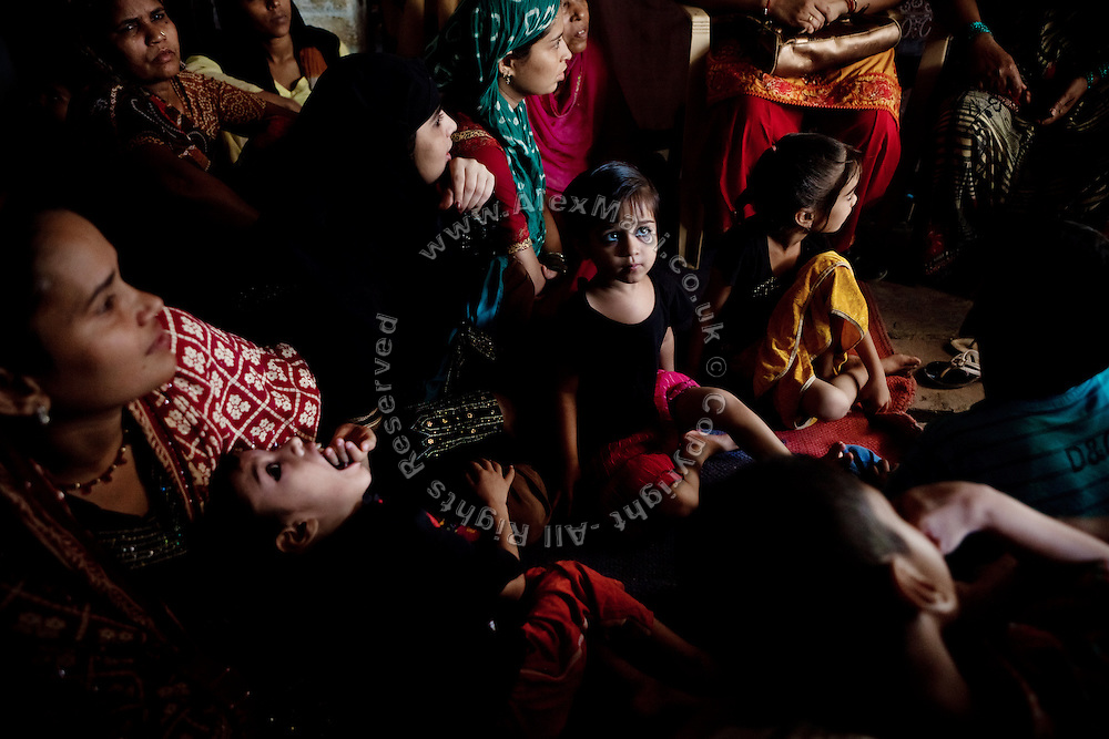 Families are being gathered at a community meeting organised by The Bhopal Medical Appeal near the abandoned Union Carbide (now DOW Chemical) factory in Bhopal, Madhya Pradesh, India, site of the infamous 1984 gas tragedy. The poisonous cloud that enveloped Bhopal left everlasting consequences that today continue to consume people's lives.