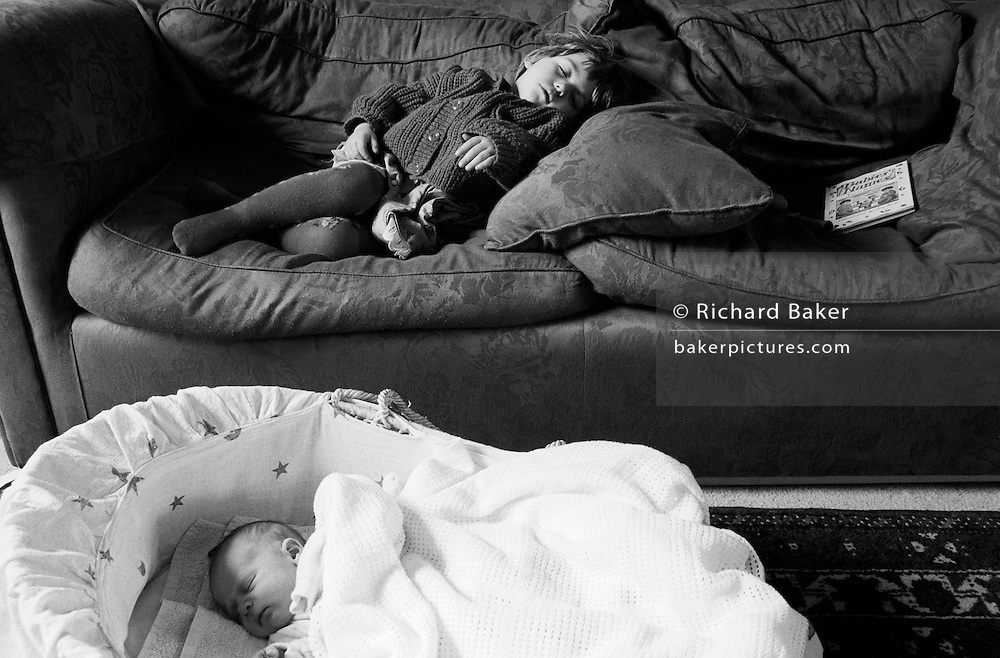 "A two and half year-old girl has a mid-afternoon sleep on the sofa of her parents' home in South London. On the floor is her young baby brother who is also enjoying some rest in his carrying basket. Both are unconscious but getting welcome shut-eye from their activities. Next to the girl is a book with the title 'Babies' Names' because her mum and dad have six weeks, under British law, in which to register a baby's birth and give it a name. From a personal documentary project entitled ""Next of Kin"" about the photographer's two children's early years spent in parallel universes. Model released."