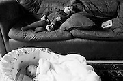 """A two and half year-old girl has a mid-afternoon sleep on the sofa of her parents' home in South London. On the floor is her young baby brother who is also enjoying some rest in his carrying basket. Both are unconscious but getting welcome shut-eye from their activities. Next to the girl is a book with the title 'Babies' Names' because her mum and dad have six weeks, under British law, in which to register a baby's birth and give it a name. From a personal documentary project entitled """"Next of Kin"""" about the photographer's two children's early years spent in parallel universes. Model released."""