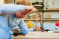 A cabinetmaking student working on carving details into a piece of wood.