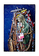 """SHOT 1/31/10 1:47:52 PM - Rosaries and pictures of loved ones adorn a Virgin Mary high atop a hillside near Ciudad Obregon, Mexico along Highway 15. The site is a popular destination to leave well wishes and thanks by family members. The Virgin of Guadalupe has symbolized the Mexican nation since Mexico's War of Independence. Our Lady of Guadalupe (Spanish: Nuestra Señora de Guadalupe) is a celebrated Catholic icon of the Virgin Mary also known as the Virgin of Guadalupe (Spanish: Virgen de Guadalupe). The Lady of Guadalupe is of significant importance to Mexican Catholics and has been given the titles of """"Queen of Mexico"""", """"Empress of the Americas"""", and """"Patroness of the Americas"""". Roadside capillas, or tiny chapels, in the Mexican states of Nayarit, Sinaloa and Sonora. The capillas are common along the roads and highways of Mexico which is heavily Catholic and are often dedicated to certain patron saints or to the memory of a loved one that has passed away. Often times they contain prayer candles, pictures, personal artifacts or notes. (Photo by Marc Piscotty / © 2010)"""