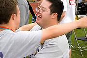 Winning athletes hugging at award ceremony. Special Olympics U of M Bierman Athletic Complex. Minneapolis Minnesota USA
