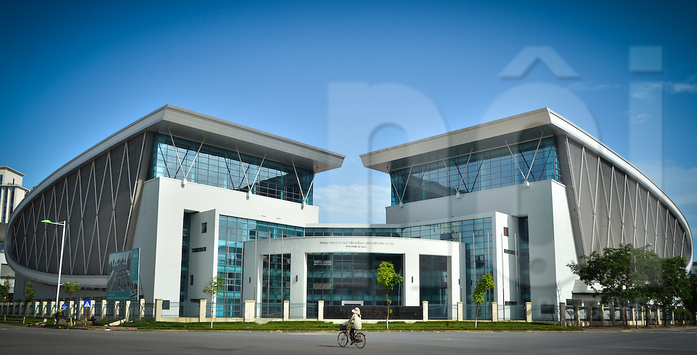 A women is riding her bicycle in front of the training centre for high-level athletes in Hanoi, My Dinh district, Vietnam, Asia. This is a modern architecture, composed with two curved buildings.