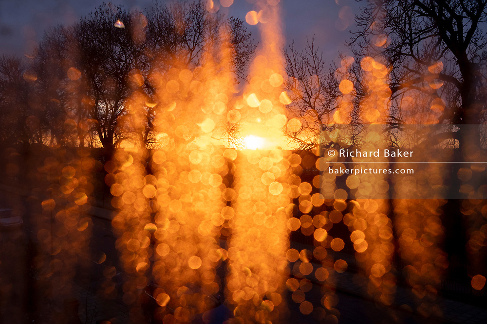 Warm, orange light from a late, flaring sunset shines through condensation in a window that overlooks a residential street and tall trees in south London, on 12th February 2021, in London, Ebngland.