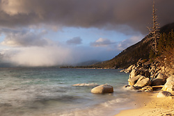 """""""Lake Tahoe Shoreline"""" - Photograph of a distant snow shower happening over Lake Tahoe, shot from a beach just North of the Thunderbird Lodge."""