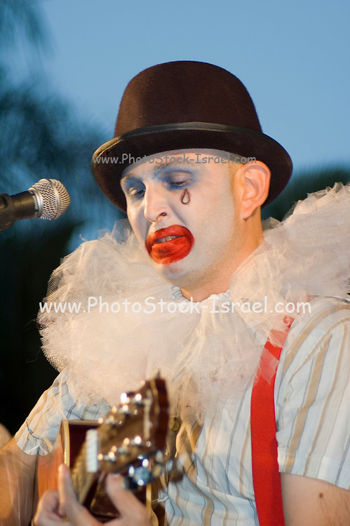 Musicians dressed and made up as a clown playing a guitar on stage
