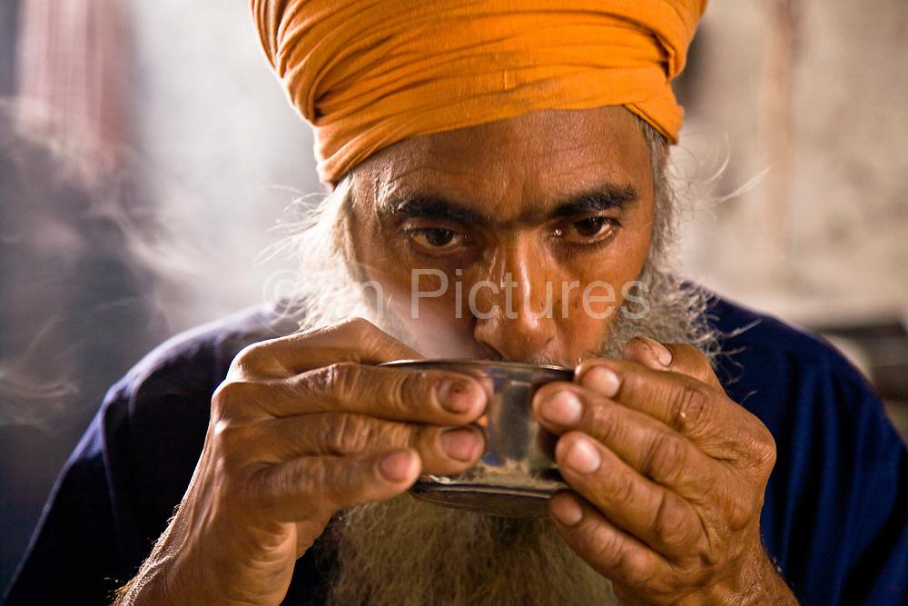 A Sikh man eats a bowl of lentil soup at the Golden Temple's Langar, Amritsar, Punjab, India