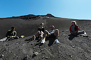 Group of tourists and local guide resting while hiking down Pico Fogo, Fogo Island, Cape Verde, West Africa.
