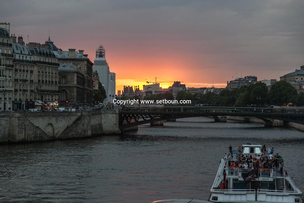 France. Paris Bateau mouche on the Saine river at sunset , in the distance , Saint louis island , ile de la cite