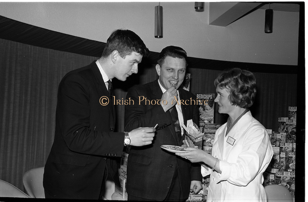 """07/02/1964<br /> 02/07/1964<br /> 07 February 1964<br /> Erin Foods Reception for launch of """"Redichips"""" at the Sybaris Club, Abbey Street, Dublin. Pictured are Miss Margaret Scott, (Ballyforan, Ballinasloe) Laboratory Technician, Erin Foods Tuam Factory of the Irish Sugar Co., serving the new Erin """"Redichips"""" to Mr William Higgins (Sales Supervisor) and Mr Pat Jones (General Sales Manager) at the launch."""