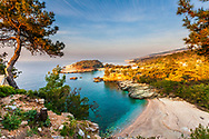 Picturesque beach with emerald sea water by a cedars forest