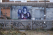 Street art mural of iconic local band Black Sabbath looking across overgrown and disused waste ground, which seems to have stalled awaiting redevelopment in the last year in the industrial area of Deritend, which lies less than half a mile from the city centre on 14th December 2020 in Birmingham, United Kingdom. Birmingham is undergoing a massive transformation called the Big City Plan which involves the controversial regeneration of the city centre as well as a secondary zone reaching out further. The Big City Plan is the most ambitious, far-reaching development project being undertaken in the UK. The aim for Birmingham City Council is to create a world-class city centre by planning for the next 20 years of transformation.