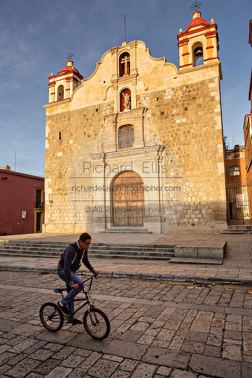 A bicyclist passes the Templo de la Preciosa Sangre de Cristo or Temple of the Blood of Christ in the historic district in Oaxaca, Mexico.