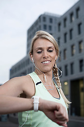 Mid adult woman checking the time after exercising and listening to music, Bavaria, Germany