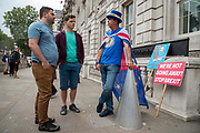 Anti Brexit campaigner Steve Bray discusses Brexit with two tourists outside the Cabinet Office in Whitehall as Ministers hold a Brexit Cabinet meeting on 16th August 2019 in London, United Kingdom.