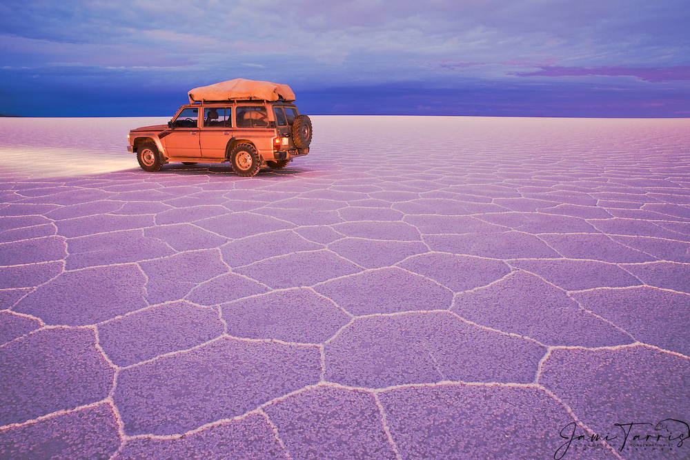 Tourist vehicle sitting on salt hexagon patterns awash in twilight pink and blue on the Salar de Uyuni,  Bolivia,South America