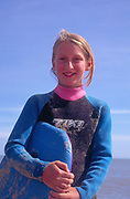 AJDM61 Girl in wet suit on beach against blue sky