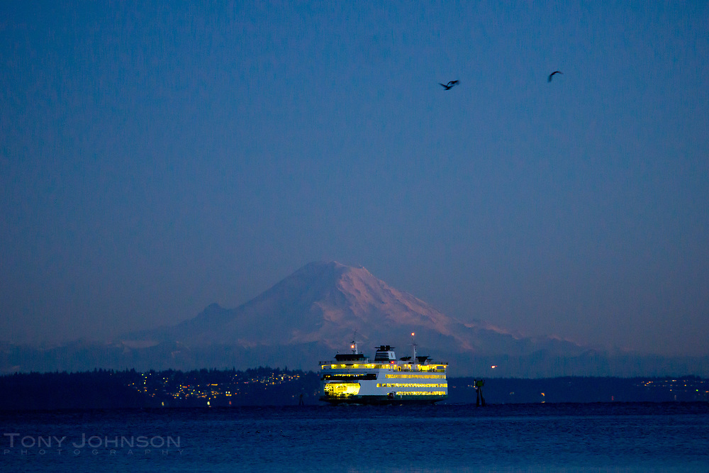 The Seattle to Bainbridge Island Ferry pulls into Eagle Harbor in front of Mount Rainier on an evening commuter run.