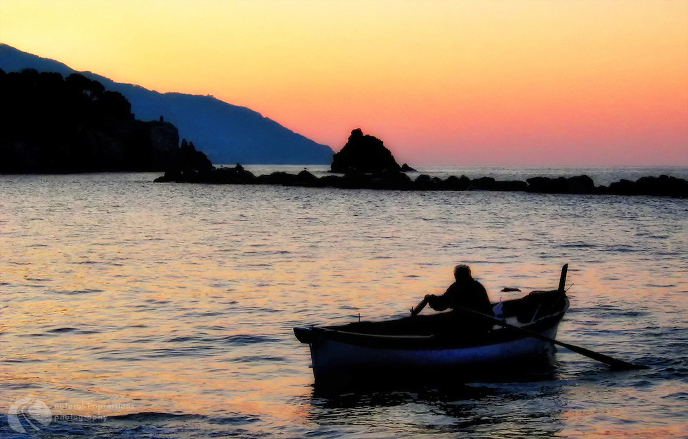 A fisherman begins his day at sunrise from the little town of Monterosso, the northernmost village in the chain of 5 villages that make up Cinque Terre, Italy.