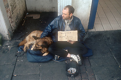 Homeless man sitting in street with pet dog; begging,