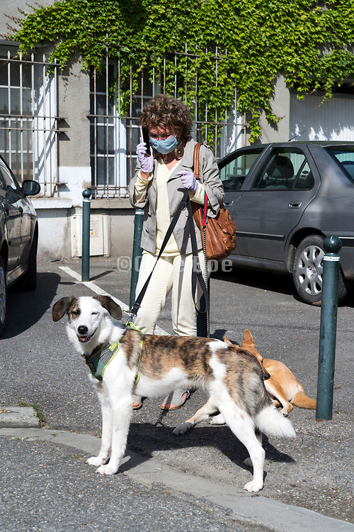 woman with dogs talking on her phone during the Covid 19 crisis and lockdown France Limoux April 2020