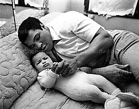 Mohammed Ali, World Heavyweight boxing champion, seen with his baby daughter Hana at his Chicago home, USA. February 1977.Photograph by Terry Fincher