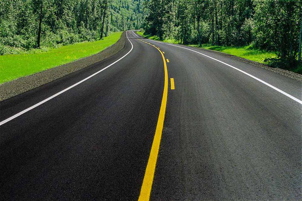 A gently curving road with no traffic winding through forested green mountains.