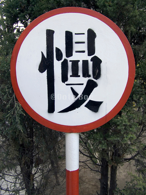 traffic warning sign with in Chinese calligraphy saying SLOW