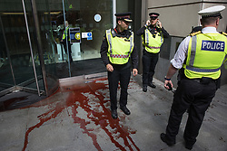 London, UK. 27th August, 2021. City of London Police investigate after fake blood was spread by an environmental activist from Extinction Rebellion outside the offices of law firm Debevoise & Plimpton LLP during a Blood Money March through the City of London. Extinction Rebellion were intending to highlight financial institutions funding fossil fuel projects, especially in the Global South, as well as law firms and institutions which facilitate them, whilst calling on the UK government to cease all new fossil fuel investment with immediate effect.