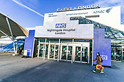 A girl wearing protective face mask walks in front of NHS Nightingale Excell Centre makeshift hospital in East London on Thursday, March 26, 2020. The British Government announced on Tuesday, that the ExCel Center in east London will become a 4,000-bed temporary hospital to deal with future coronavirus patients. (Photo/Vudi Xhymshiti)