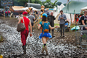 A couple dressed to party, ignoring the mud after heavy rain created a mud bath at Glastonbury Festival 2016, United Kingdom. Glastonbury Festival is the largest greenfield festival in the world, and is now attended by around 175,000 people. Its a five-day music festival that takes place near Pilton, Somerset. In addition to contemporary music, the festival hosts dance, comedy, theatre, circus, cabaret, and other arts. Held at Worthy Farm in Pilton, leading pop and rock artists have headlined, alongside thousands of others appearing on smaller stages and performance areas.