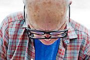 senior man using two glasses to read