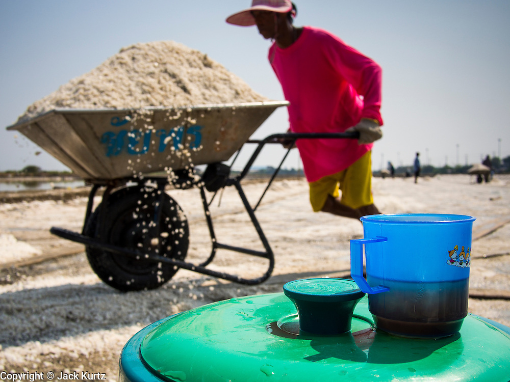 """28 MARCH 2014 - NA KHOK, SAMUT SAKHON, THAILAND:  A worker in a salt field pushes a wheel barrow of salt past a cooler of iced tea. Thai salt farmers south of Bangkok are experiencing a better than usual year this year because of the drought gripping Thailand. Some salt farmers say they could get an extra month of salt collection out of their fields because it has rained so little through the current dry season. Salt is normally collected from late February through May. Fields are flooded with sea water and salt is collected as the water evaporates. Last year, the salt season was shortened by more than a month because of unseasonable rains. The Thai government has warned farmers and consumers that 2014 may be a record dry year because an expected """"El Nino"""" weather pattern will block rain in mainland Southeast Asia. Salt has traditionally been harvested in tidal basins along the coast southwest of Bangkok but industrial development in the area has reduced the amount of land available for commercial salt production and now salt is mainly harvested in a small parts of Samut Songkhram and Samut Sakhon provinces.    PHOTO BY JACK KURTZ"""